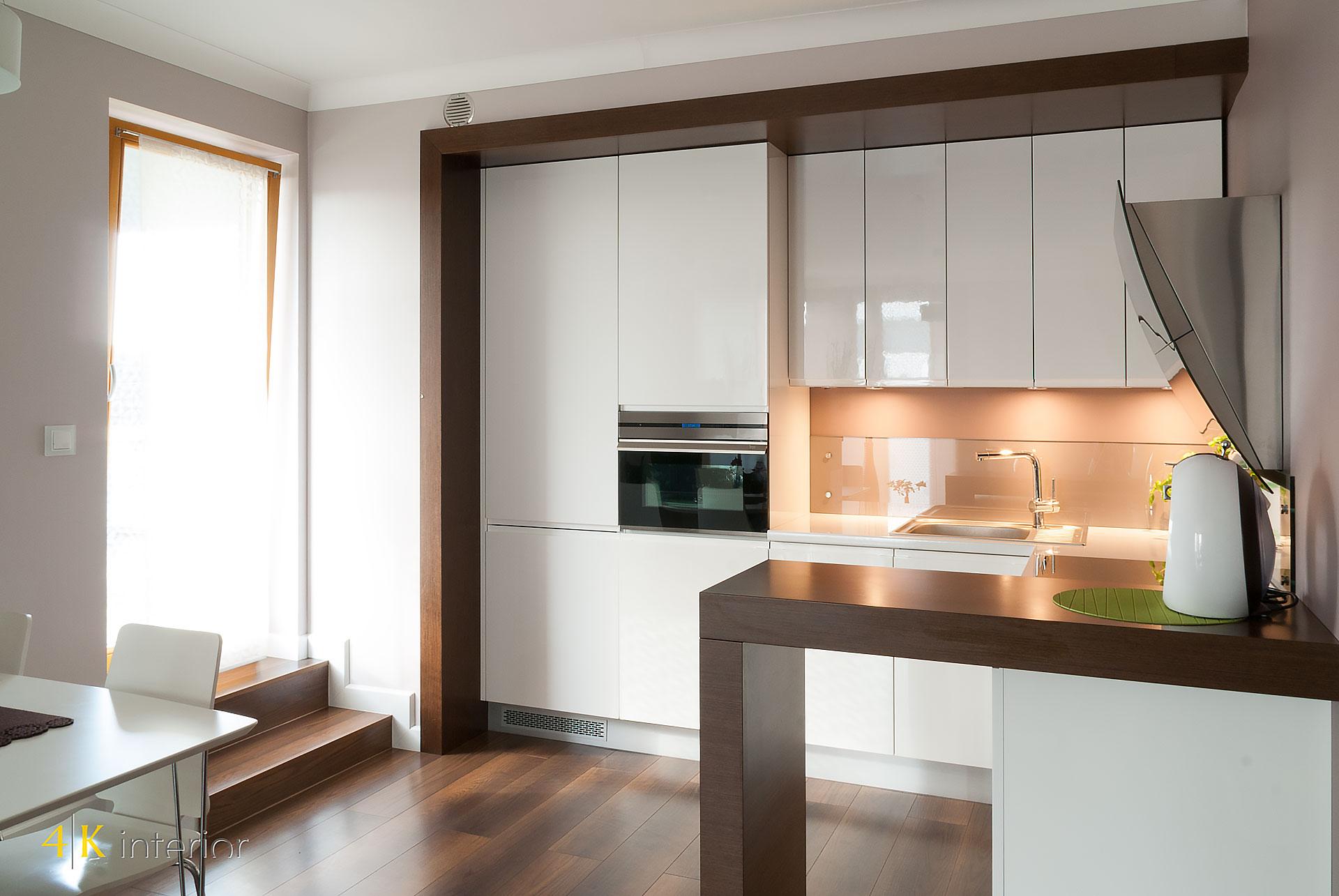 Wnętrza salonu z otwartą kuchnią w małym apartamencie 03 przeźroczyste szkło na ścianie kuchennej nad blatem, wnęka wyłożona fornirem